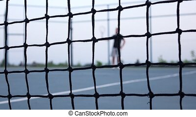 Tennis player volleys using forehand technique. Tennis net in front. Dolly shot