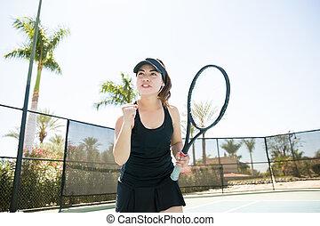 Tennis player winning a game