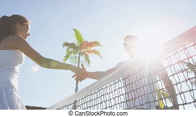 Tennis players handshake thanking each other for a game of ...
