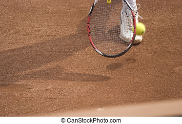 Tennis racket and ball on slag