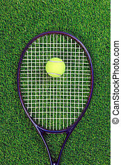 Tennis raquet and ball on grass