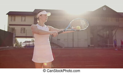 Tennis serve - woman tennis player serving playing. Tennis outside in summer. Fit female athlete practicing. Healthy active sport lifestyle.