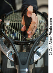 Stringing Machine. Detail of tennis stringer hands while holding awl and doing racket stringing