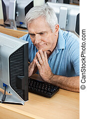 Tensed Senior Man Looking At Computer In Classroom