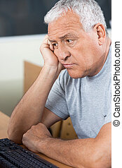 Tensed Senior Student Looking At Computer