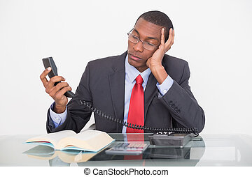 Tensed young Afro businessman looking at telephone receiver...