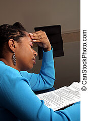 A young woman feeling the frustration while going over tax forms.