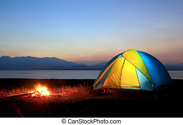 tent and campfire at sunset, beside the lake