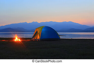 tent and campfire at sunset,beside the lake