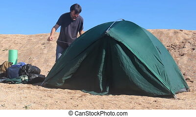 close up of a man is disassembling camping tent on the beach time lapse process
