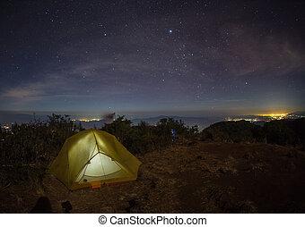 tent glows under a night sky full of stars.