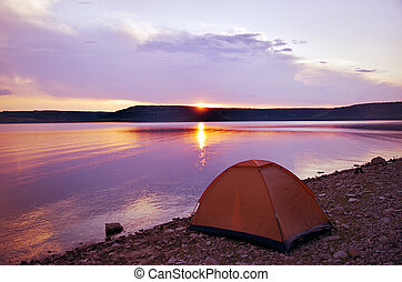 Tent near the lake at sunset