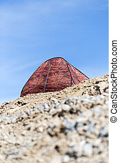 tent on a cliff on the background of blue sky