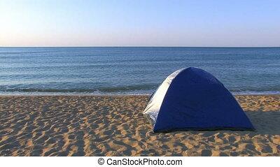 Tent on a sandy beach with sea