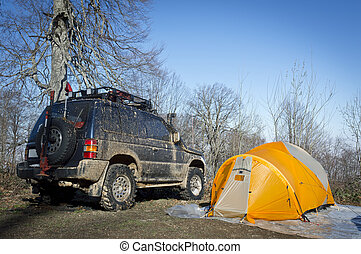 Tents and SUV car in forest at sunrise