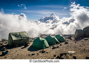 Tents over clouds for people trekking Mount Kilimanjaro,...