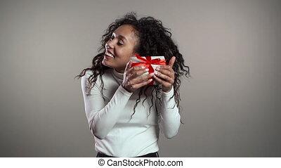tenue, coiffure, arrière-plan., sweater., sourire, noël, surpris, cadeau, femme, course, mélangé, studio, boîte, gris, girl, mood., bouclé