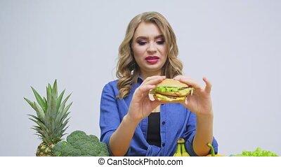 tenue, femme mange, hamburger, concept, sain, nuisible
