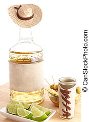 Tequila bottle sombrero and limes - Tequila bottle with...