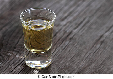 Tequila - One tequila shot on the wooden background. Close...