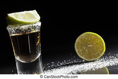 Tequila shot - Gold tequila shot with lime fruits isolated...