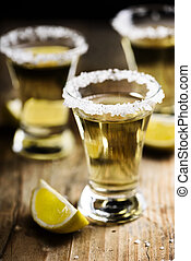 Tequila shots with salt on wooden table.