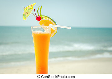 Tequila sunrise cocktail with fruits and umbrella decoration