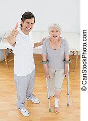 terapeut, gesturing, tommelfingre oppe, hos, senior, disabled, patient