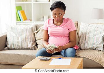 terhes nő, számolás, pénz, otthon