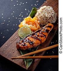Teriyaki salmon with rice on a wooden platter.