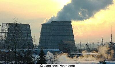 Termal station smoke in sky at winter sunset
