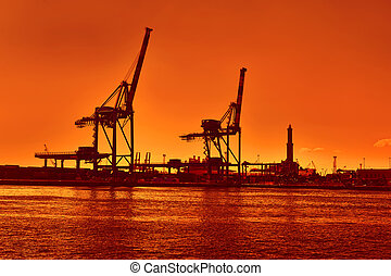 terminal cranes silhouette and forklifts in Genova port at evening