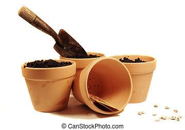 Terra Cotta Pots - a garden trowel and terracotta pots with...
