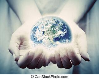 terra, shines, em, mulher jovem, hands., salvar, mundo