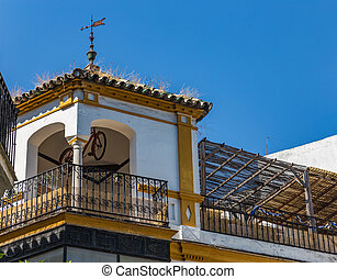 Terrace and gazebo with a hanging bike on the roof of a house in Seville, Spain.