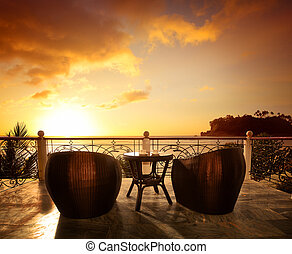 Terrace lounge with rattan armchairs and seaview in a luxury resort