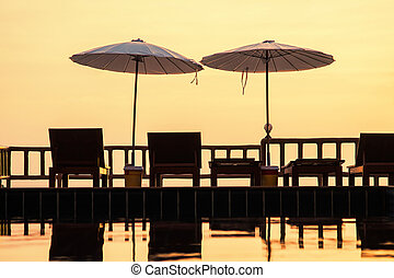 Terrace with a view on sea and sunset. Umbrellas and lounge chair in a sunlight.
