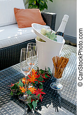 Terrace with champagne glasses and champagne bottle in...