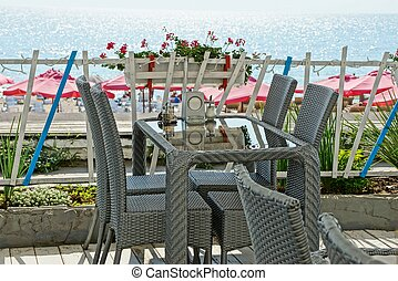 terraces of a summer restaurant with gray chairs and a glass table by the fence against the sea