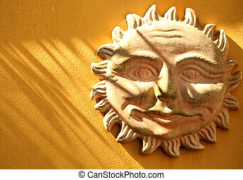 Terracotta smiling sun on a wall
