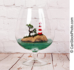 Composition with sea and beacon in a glass. Terrarium