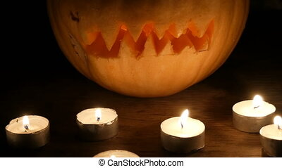 Terrible Halloween pumpkin surrounded by many candles in...