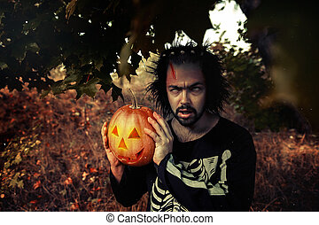 Terrible man. Human zombies holding a pumpkin in her hands. Symbol of the holiday Halloween. Skull. Zombie. Halloween mask. Scary dress for a party on Halloween. Poster.
