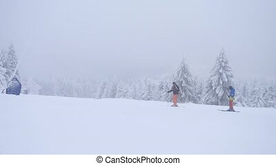 Terrible misty weather on slope in winter mountains. Few...