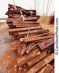 Terrible smell pile of extracted old wooden ties. Old oiled used oak railway sleepers stored after big reconstruction of old railway station.