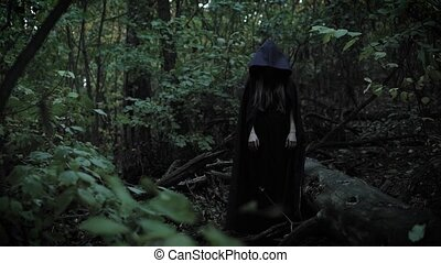 terrible sorceress is standing without movement in a forest,...
