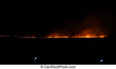 Terrible wild huge fire on the horizon at night in field. - ...
