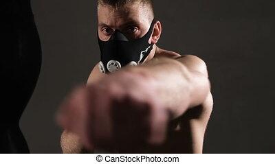 Terrible young man in a mask. Aggressive beats ahead. Boxing