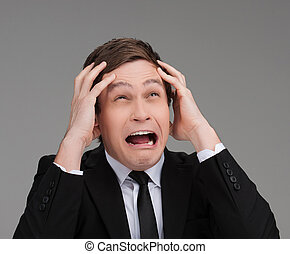 Terrified businessman. Portrait of young businessman crying...