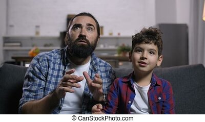 Terrified father and son watching horror movie - Scared...